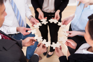 High Angle View Of Business People Assembling Jigsaw Puzzle